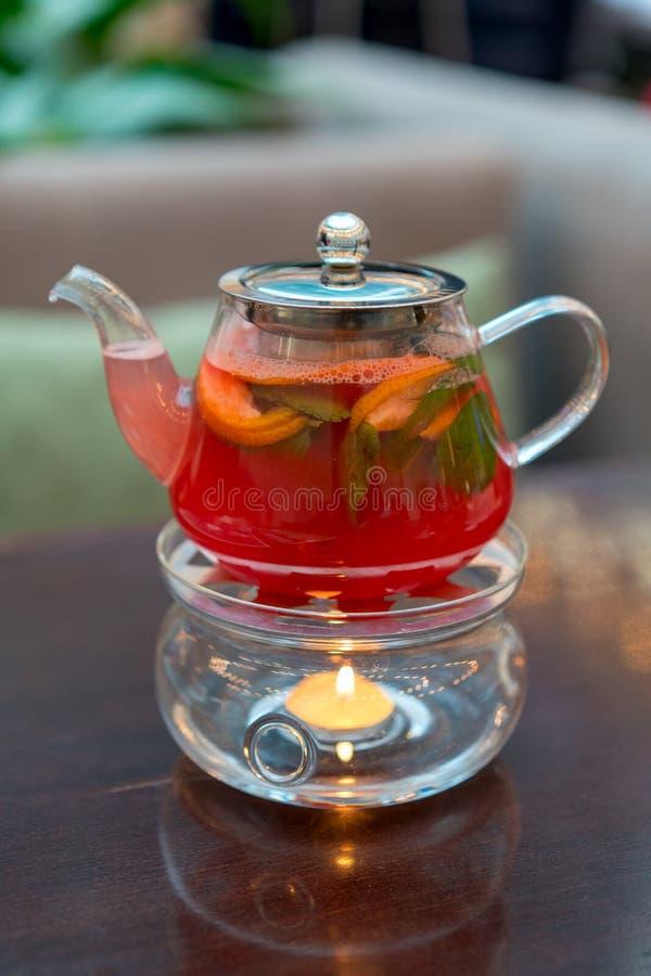 Een glastheepot met de slagen van de grapefruitthee van de vlam van a kan royalty-vrije stock afbeeldingen