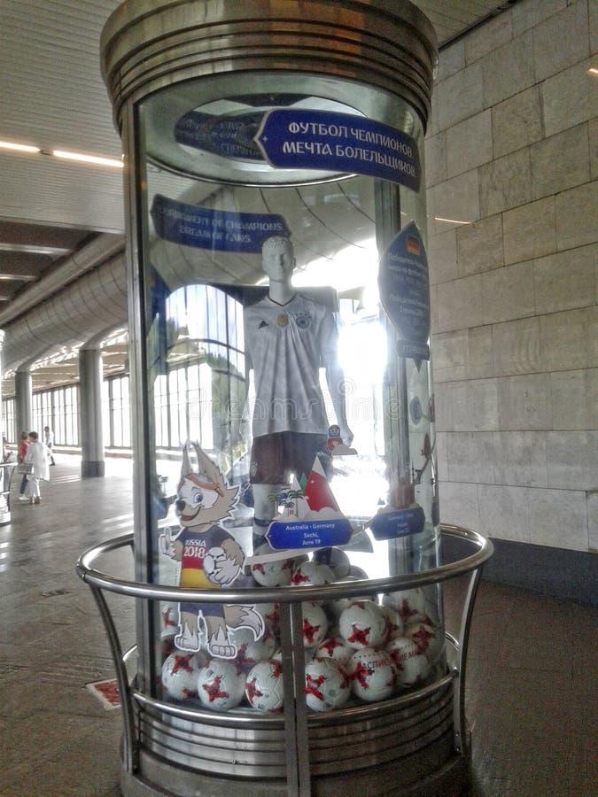 Een glasvoetstuk met de symbolen van de Federaties vormt 2017 en de Wereldbeker van 2018 in de metro post met een ledenpop in t t stock foto's