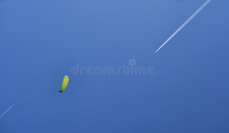 Een glijscherm met een geelgroene parashute en twee vliegtuigen royalty-vrije stock afbeeldingen
