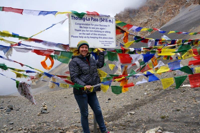 Een glimlachend meisje bevindt zich dichtbij een teken op de thorong-La Pas 5416m, de hoogste pas in de wereld nepal stock afbeeldingen