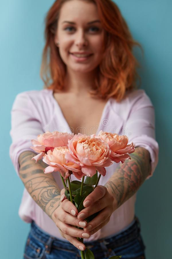 Een glimlachend meisje met een tatoegering geeft een boeket van roze rozen rond een blauwe achtergrond met exemplaarruimte De gif stock afbeeldingen