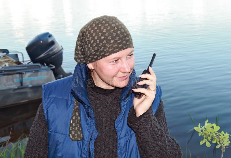 Een glimlachend meisje spreekt op een draagbare radioreeks royalty-vrije stock foto