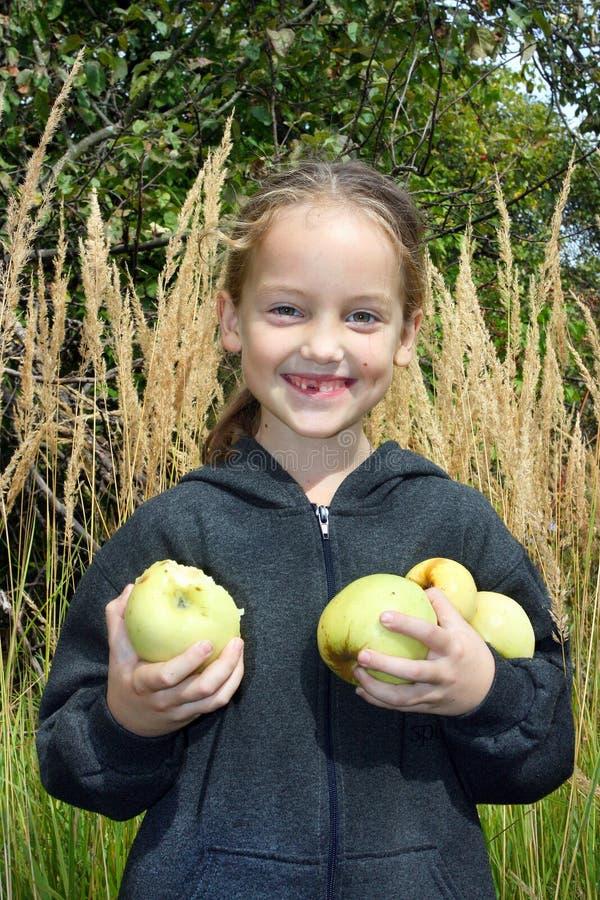 Een glimlachend meisje zonder foretooth houdt in haar handen heel wat appelen stock fotografie