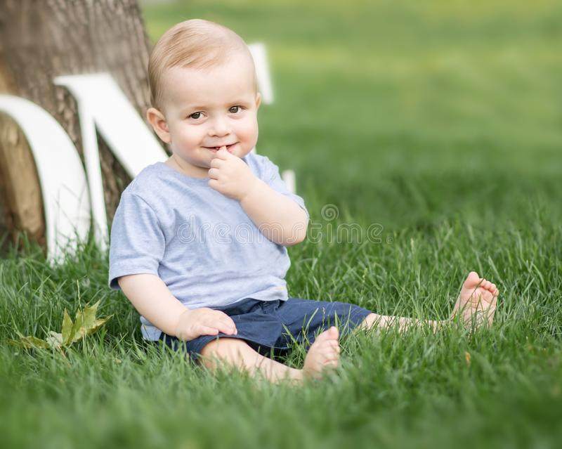 Een glimlachende aanbiddelijke kleine babyjongen die een vinger in zijn mondzitting houden op groen gras openlucht bij de zomerpa royalty-vrije stock foto