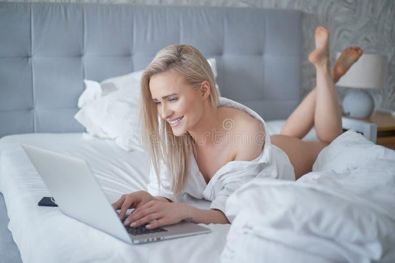 Een glimlachende blondevrouw die het bed voor haar laptop liggen royalty-vrije stock afbeeldingen