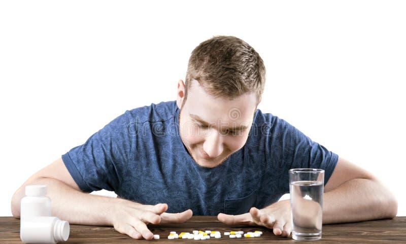 Een glimlachende die jongen met meds op een witte achtergrond wordt geïsoleerd Een patiënt die pillen met een glas water nemen Su stock foto