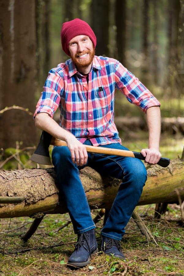 Een glimlachende gebaarde houthakker in een hoed en een overhemd met een bijl zit royalty-vrije stock fotografie