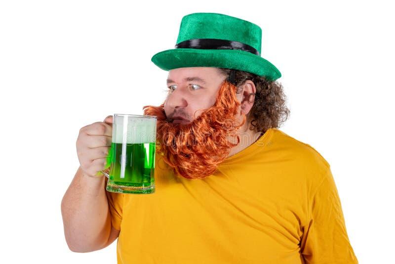 Een glimlachende gelukkige vette mens in een kabouterhoed met groen bier bij studio Hij viert St Patrick royalty-vrije stock afbeeldingen