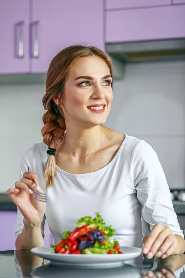 Een glimlachende gelukkige vrouw eet een gezonde plantaardige salade Concep stock fotografie