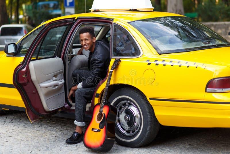 Een glimlachende jonge mens in auto met geopende deur die van gele auto, en, met linker buiten been, dichtbij gitaar kijken gliml stock foto