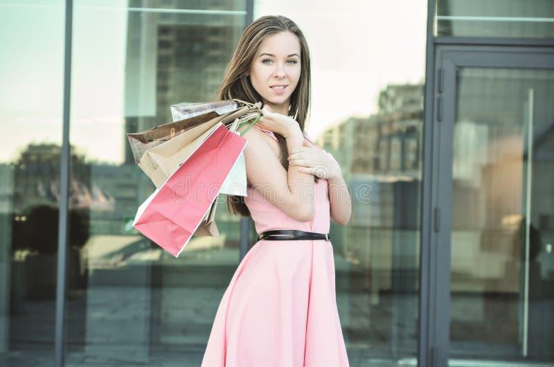Een glimlachende jonge vrouw werpt document zakken op haar schouder stock fotografie