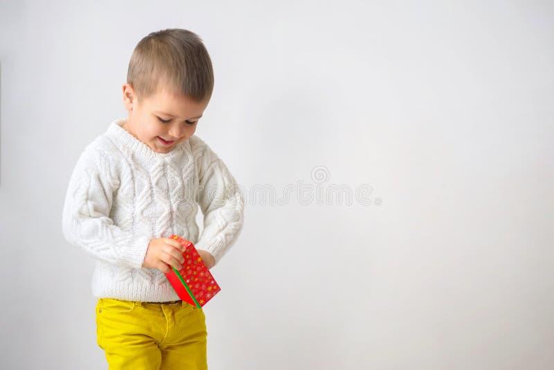 Een glimlachende jongen is neemt een gift Kind het kijken van een rode cardb stock foto's