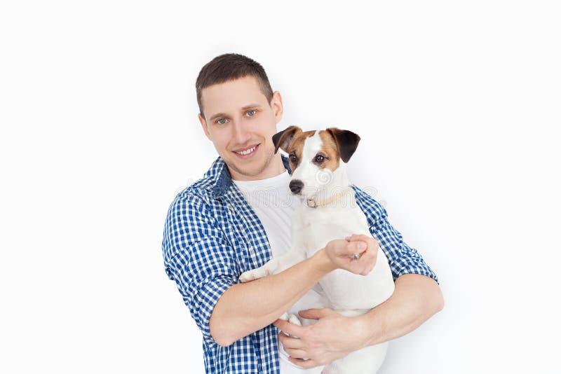 Een glimlachende knappe mens die een rashond op een witte achtergrond houden Het concept mensen en dieren jonge mens die zijn hon royalty-vrije stock foto's