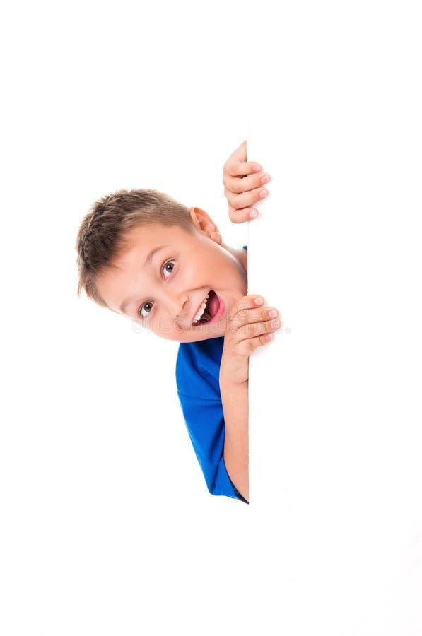 Een glimlachende knappe tienerjongen die een heldere blauwe t-shirt dragen en achter een wit die paneel stellen op witte achtergr stock fotografie