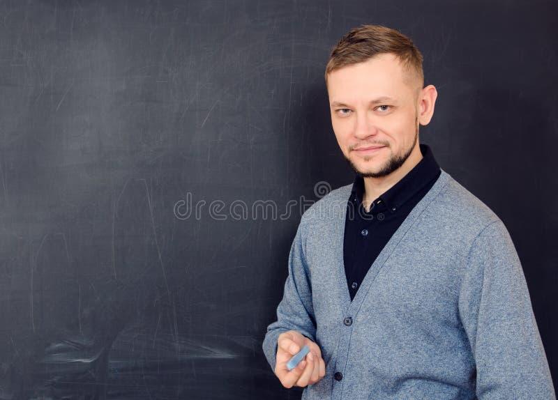 Een glimlachende mens met krijt dichtbij een schoolraad stock foto's