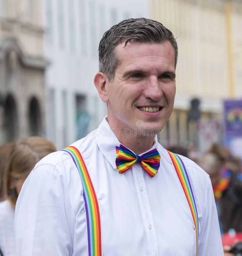 2019: Een glimlachende mens met een regenboog die bowtie die de Gay Pride-parade bijwonen ook als Christopher Street Day-CDD in M stock foto