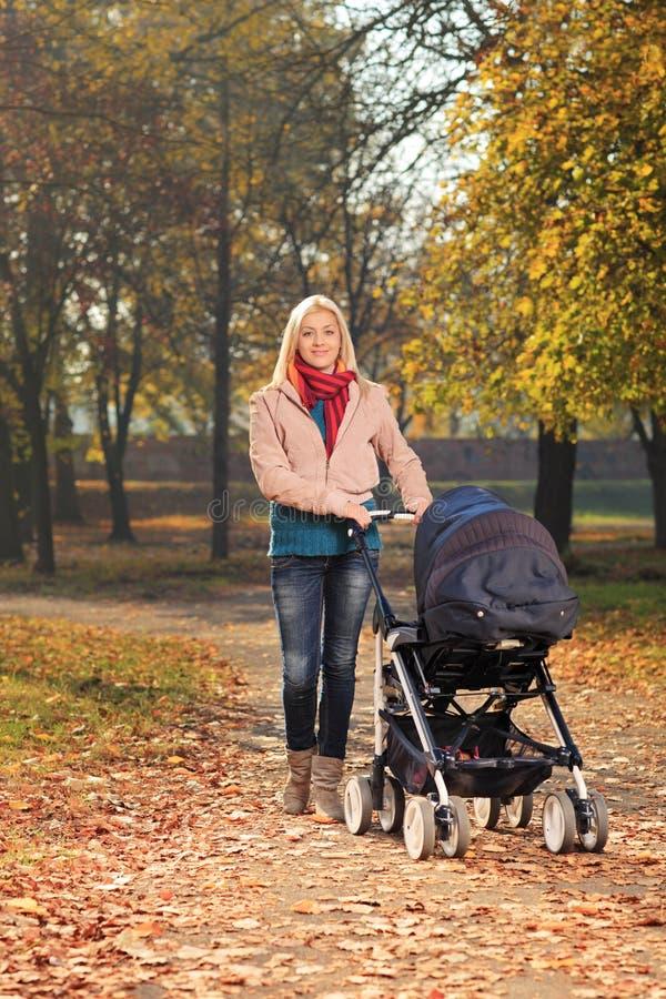 Een glimlachende moeder met een kinderwagen die een gang in een park hebben stock afbeeldingen