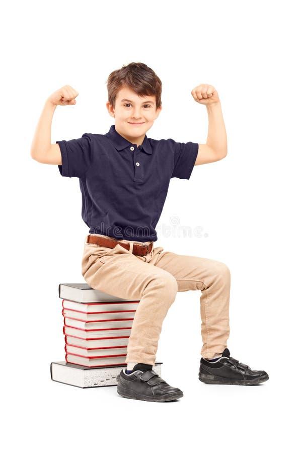 Een glimlachende schooljongen die zijn spieren gezet op een stapel van boek tonen royalty-vrije stock afbeelding