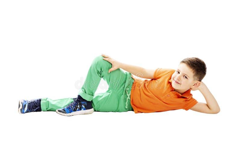 Een glimlachende schooljongen in een oranje T-shirt ligt aan zijn kant Ge?soleerd op een witte achtergrond stock fotografie