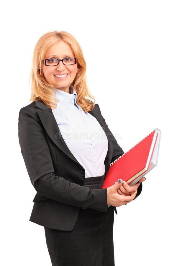 Een glimlachende vrouwelijke leraar die een notitieboekje houdt stock foto's