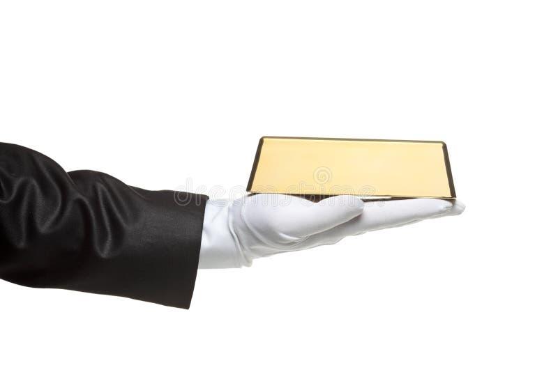Een gloved hand die een gouden staaf houdt stock foto