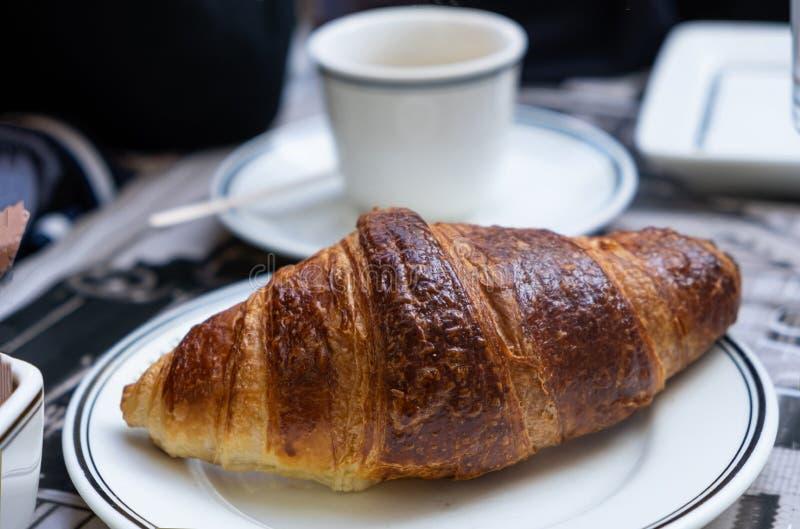 Een goed gefundeerde croissant op wit gerecht in de close-up Blauwkopje op een schotel achtergrond royalty-vrije stock foto's
