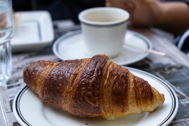 Een goed gefundeerde croissant op wit gerecht in de close-up Blauwkopje op een schotel achtergrond royalty-vrije stock fotografie