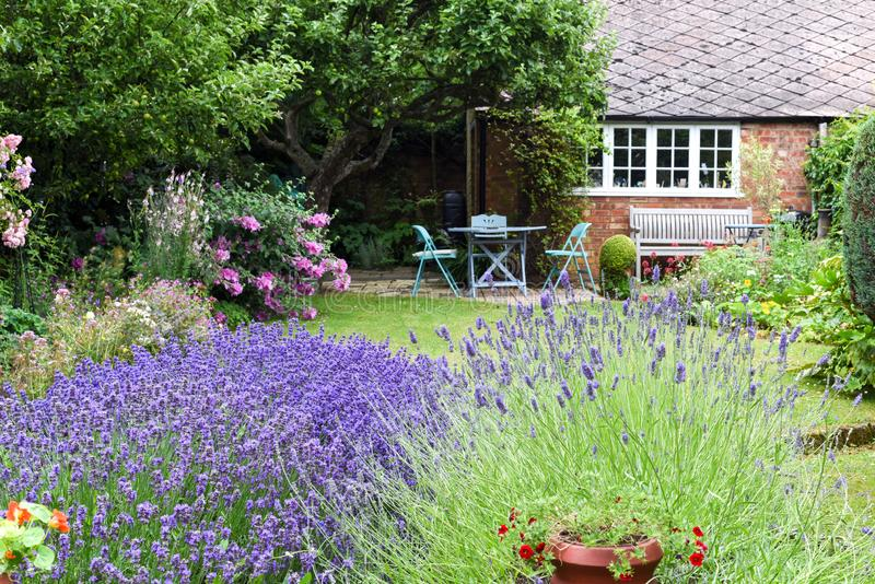 Een goed gehouden achteryard of een tuin met gazon, bloemen en plaatsingsgebied royalty-vrije stock fotografie