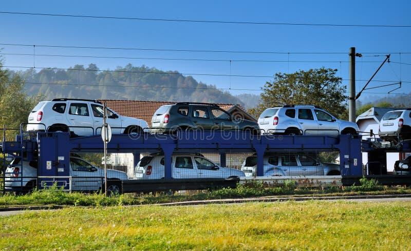 Een goederentrein met auto's wordt geladen die stock afbeelding