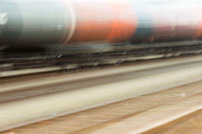 Een goederentrein met oranje en blauwe wagens gaat snel over stock illustratie