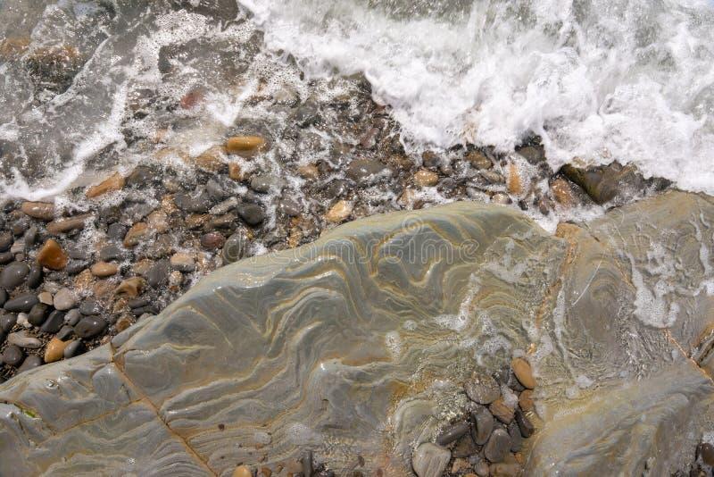 Een golf rolt op een rotsachtig overzees strand stock afbeelding