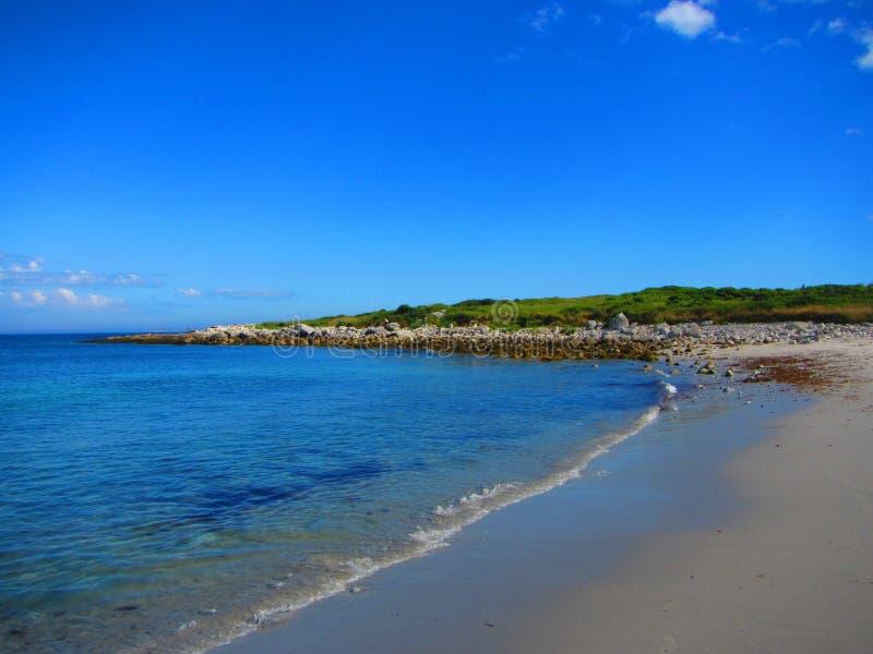 Een golf wast kust bij een strand stock afbeeldingen