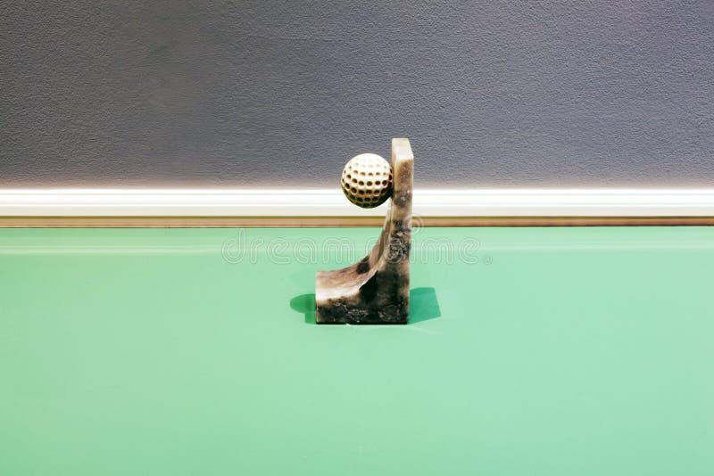 Een golfbal met een marmeren basis op bovenkant een glas groene lijst als abstracte installatie stock afbeeldingen