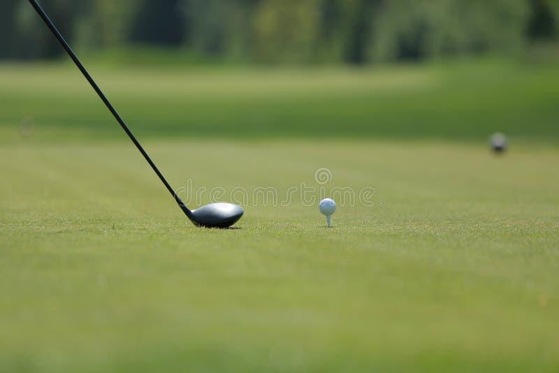 Een golfbestuurder met bal op een T-stuk op de golfcursus stock foto