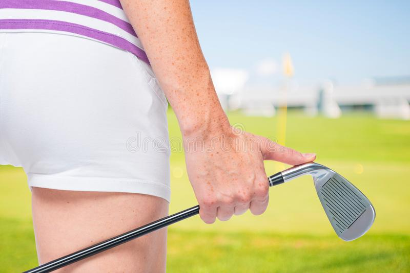 Een golfclub in de handen van een jong vrouwelijk atletenclose-up stock afbeelding