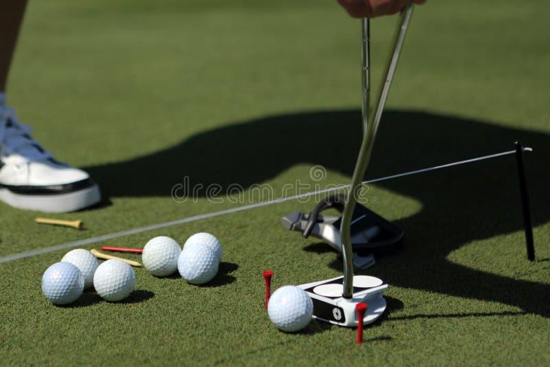 Een golfspeler met het zetten en ballen dichtbij een zaal stock afbeelding