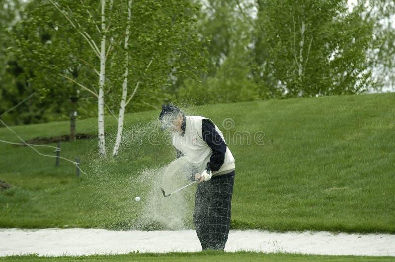 Een golfspeler slaat uit een bal stock afbeeldingen