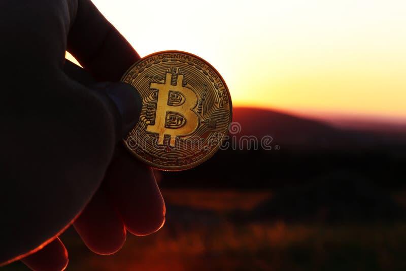 Een gouden bitcoin in hand tegenover zonsondergang en bergen binnen ver stock afbeelding