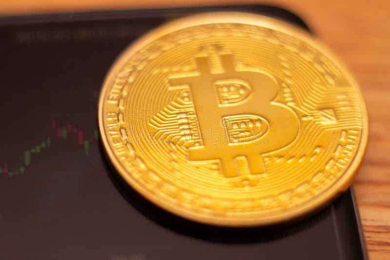 Een gouden bitcoin op grafiek en diagrammenachtergrond concept handelcrypto munt stock afbeelding
