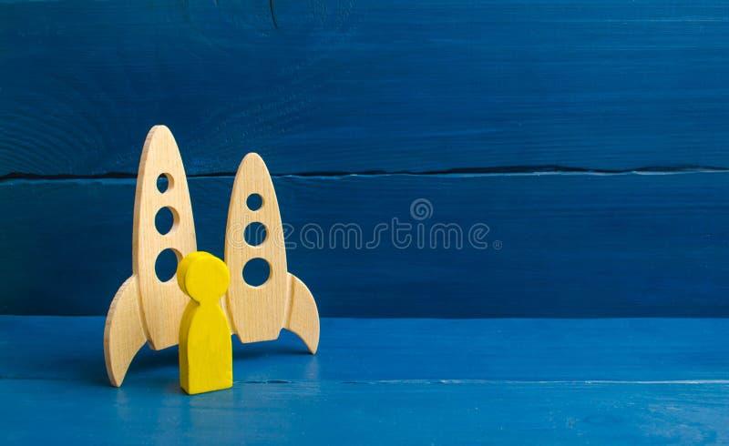 Een gouden mens bevindt zich dichtbij raketten Selectie van kandidaten voor vlucht in ruimte De eerste commerciële vlucht aan de  stock afbeeldingen