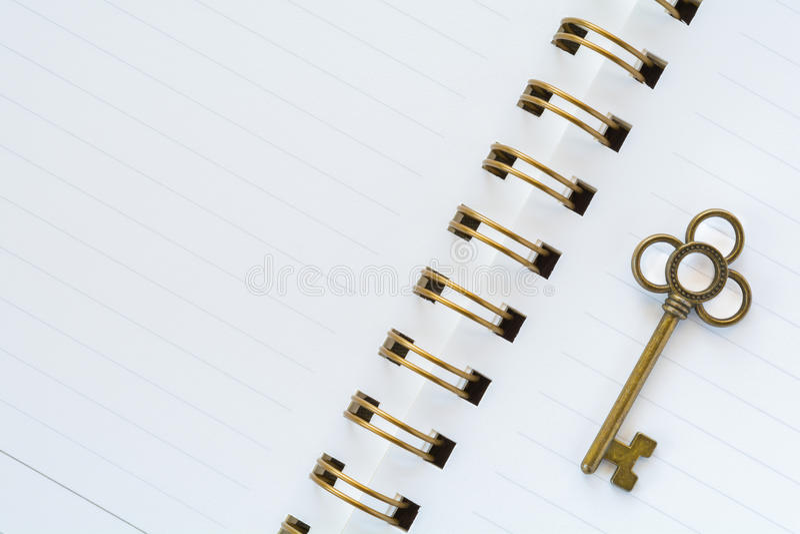 Een gouden metaalsleutel op Witboek stock afbeeldingen