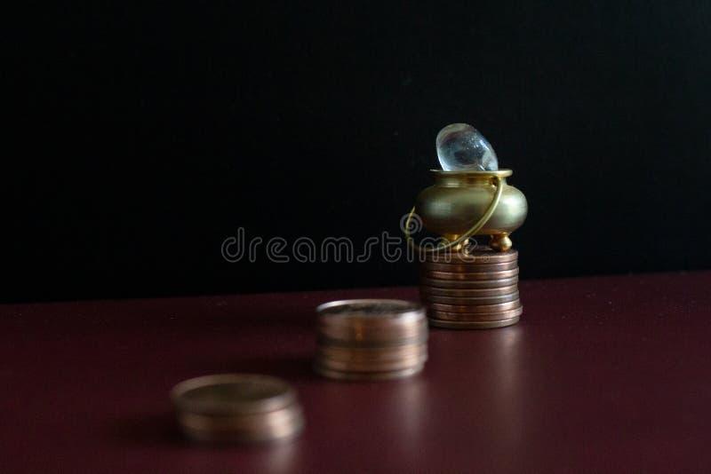 Een gouden pot met een halfedelsteen bovenop een stapel geldmuntstukken stock fotografie