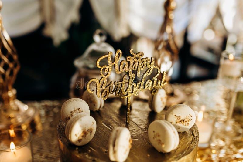 Een gouden verjaardagscake is verfraaid met macaroni stock afbeeldingen