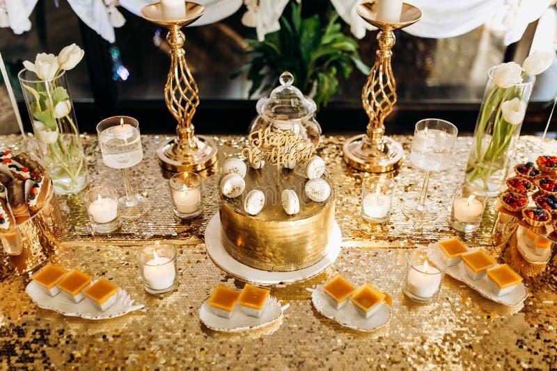 Een gouden verjaardagscake is verfraaid met macaroni stock foto