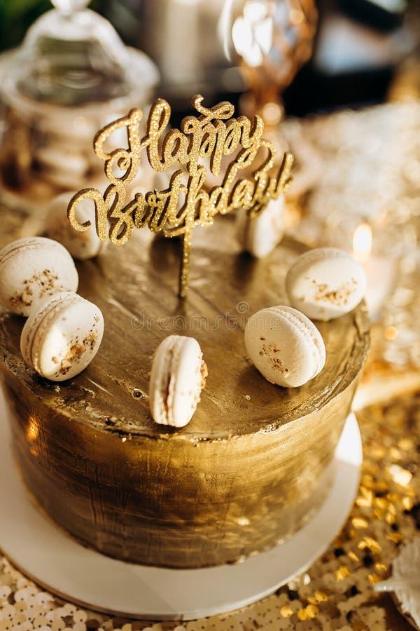 Een gouden verjaardagscake is verfraaid met macaroni royalty-vrije stock foto