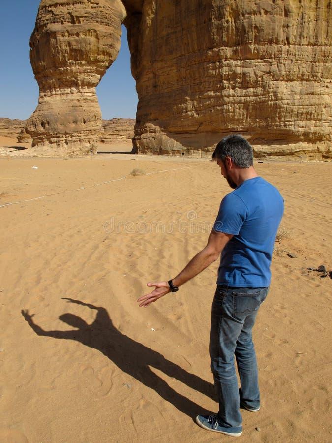 Een grappig beeld van een mens die met zijn eigen schaduw voor de Olifantsrots debatteren in Saudi-Arabië KSA royalty-vrije stock fotografie
