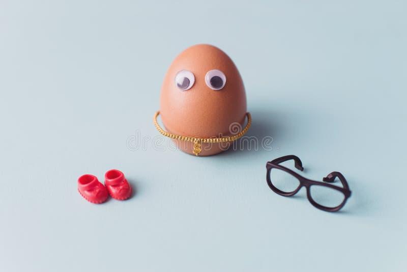 Een grappig leuk bruin ei met zwarte glazen en rode schoenen op blauwe achtergrond royalty-vrije stock afbeeldingen