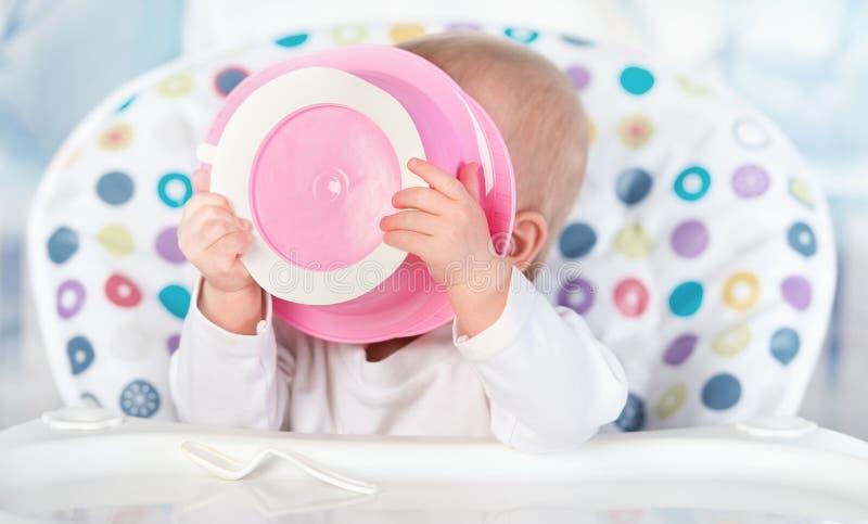 De grappige baby eet van roze plaat royalty-vrije stock afbeeldingen