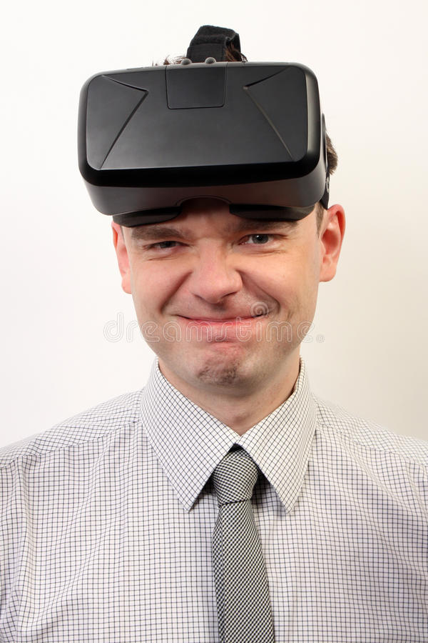Een grappige mens die Oculus-hoofdtelefoon van de Spleetvr de virtuele werkelijkheid, dragen die rond voor de gek houden stock afbeelding