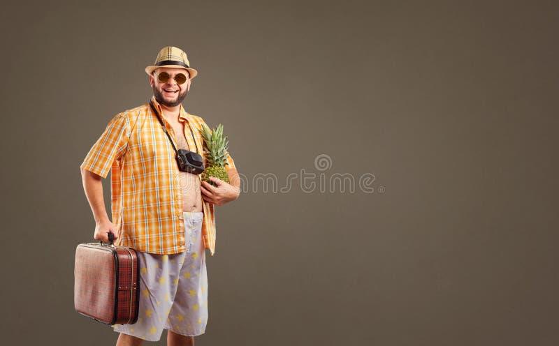 Een grappige vette gebaarde toerist met een ananas en een koffer smil stock afbeeldingen